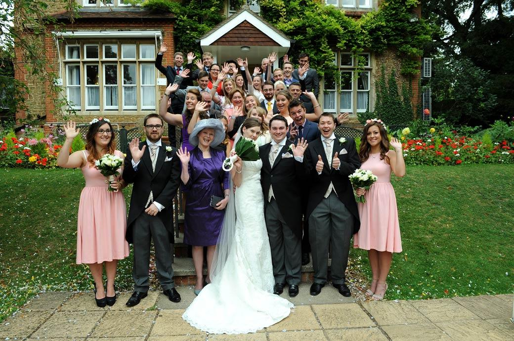 Everyone happily waving on the steps group wedding photo captured by Surrey Lane wedding photographers at the ever popular Guildford Register Office
