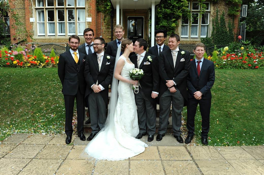 Newly-weds kiss as the gents look on and laugh in this group wedding picture taken at the foot of the steps in the garden at Surrey wedding venue Guildford Register Office