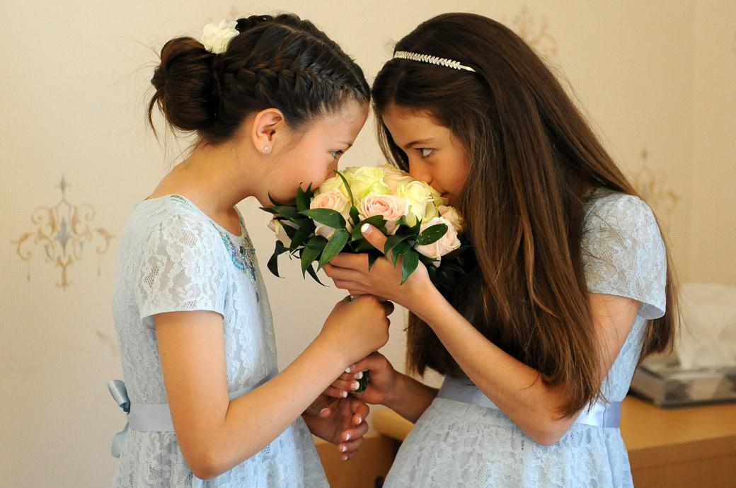 Cute wedding photograph of two little bridesmaids smelling the wedding bouquet captured at Surrey venue Guildford Register Office in Artington House Surrey