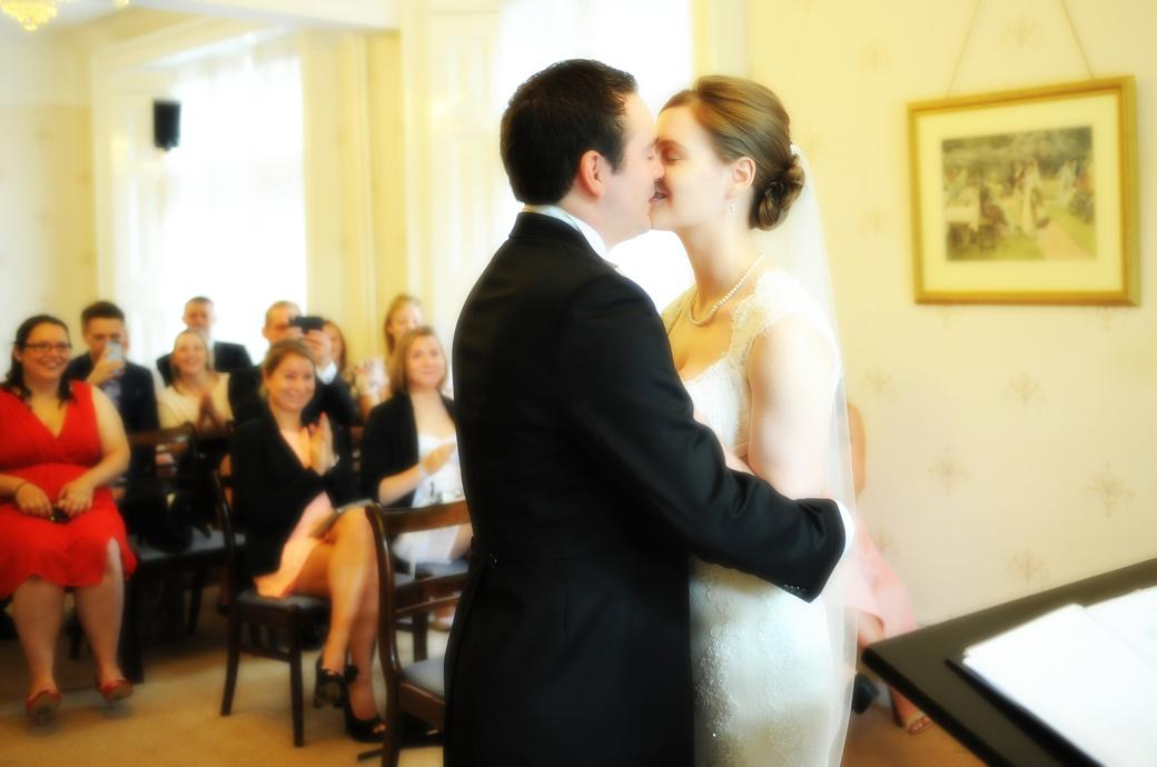 A passionate loving kiss captured in this wedding picture taken in the Guildown Room by a Surrey Lane wedding photographer at the ever popular Guildford Register Office