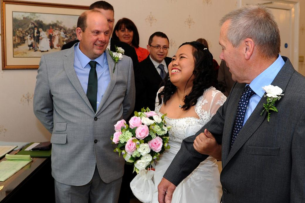 Wedding picture of an excited Bride as she meets a happy smiling Groom at Surrey wedding venue Guildford Register Office Artington House in the Guildown Room