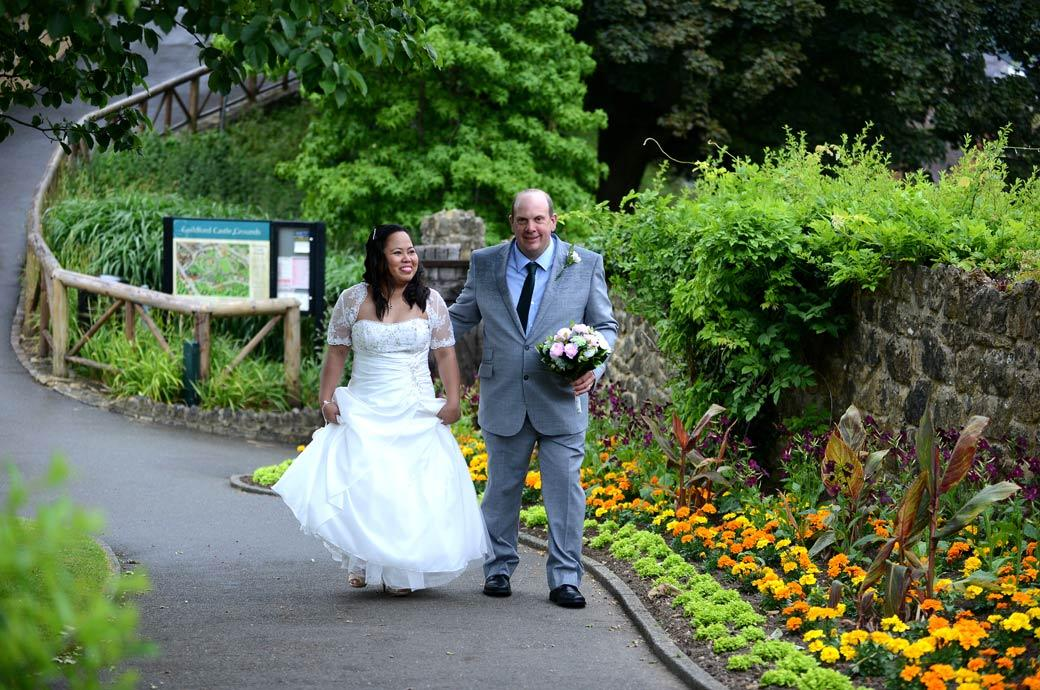 Beaming happy bride and groom walking along a path through the Surrey popular historical and pretty tourist spot Guildford Castle Gardens after their Artington House marriage
