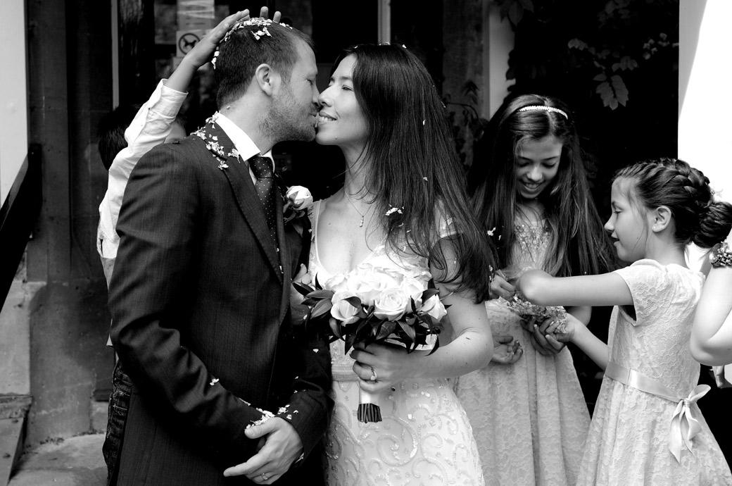A lingering newlywed kiss at Guildford Register Office on the steps of Artington House Surrey as the children hurry to get more confetti to throw over the newlyweds