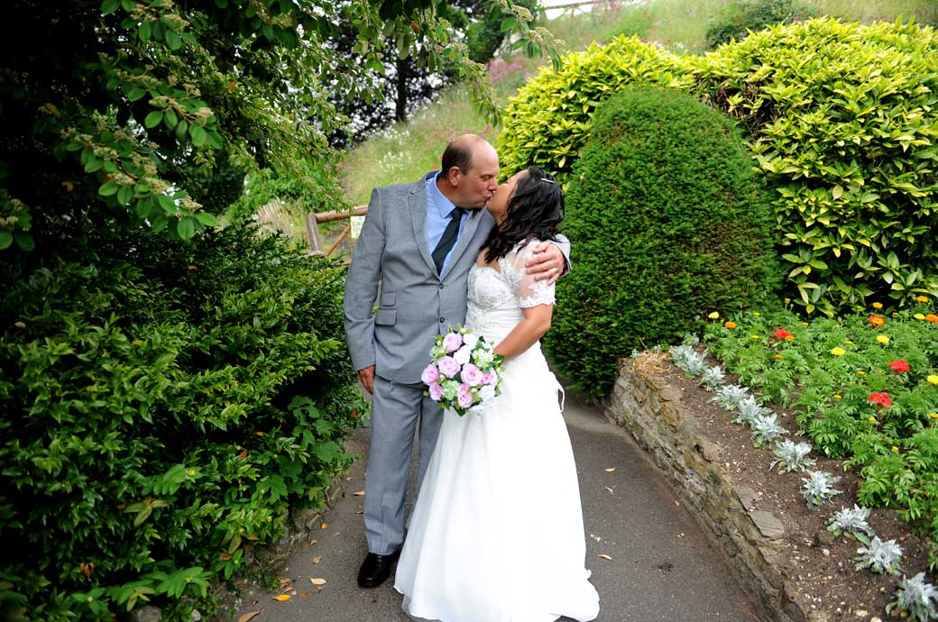 A wedding photograph of a Bride and Groom kissing on a path through the pretty gardens  at the popular tourist destination Guildford Castle in Surrey