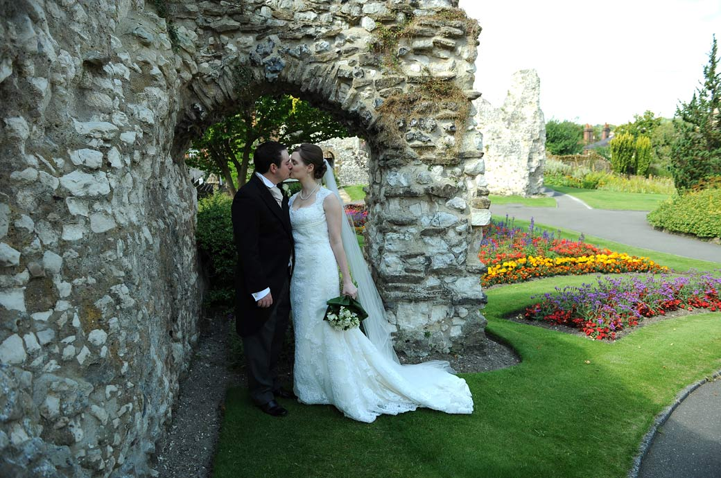 A beautiful romantic and tender wedding photograph of the newly-weds kissing by a stone arch in the beautiful Guildford Castle Gardens in Surrey