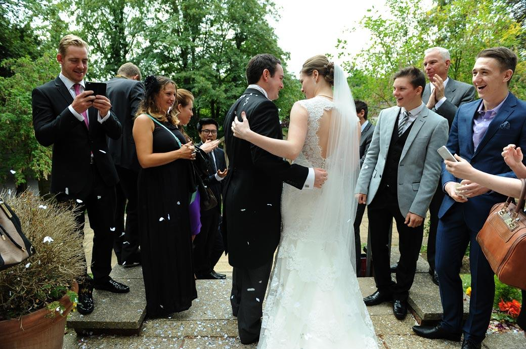 Guests laugh along with the newly-weds after the confetti throwing captured in this wedding photograph taken on the Guildford Register Office steps in Surrey