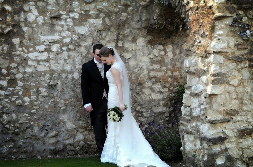 Elegance of the Bride as she bows her head standing before her husband and the ancient walls of Guildford Castle Gardens captured in this Surrey wedding photo