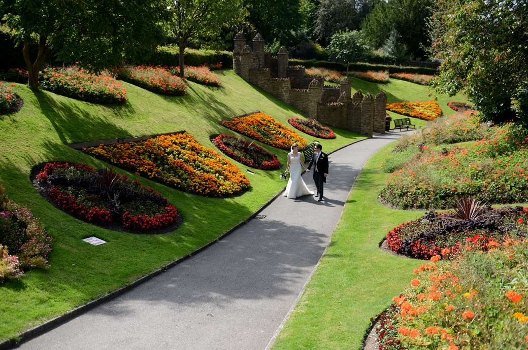 Bird's eye wedding photo of a Surrey newly-wed couple walking holding hand in hand past the beautiful and colourful Guildford Castle Gardens flower beds