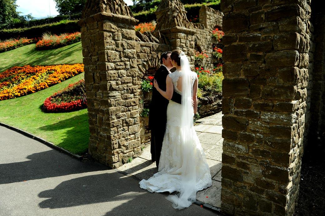 Newly-weds romantically kissing arm in arm by a stone wall in the colourful Guildford Castle Gardens captured in this natural Surrey wedding photograph