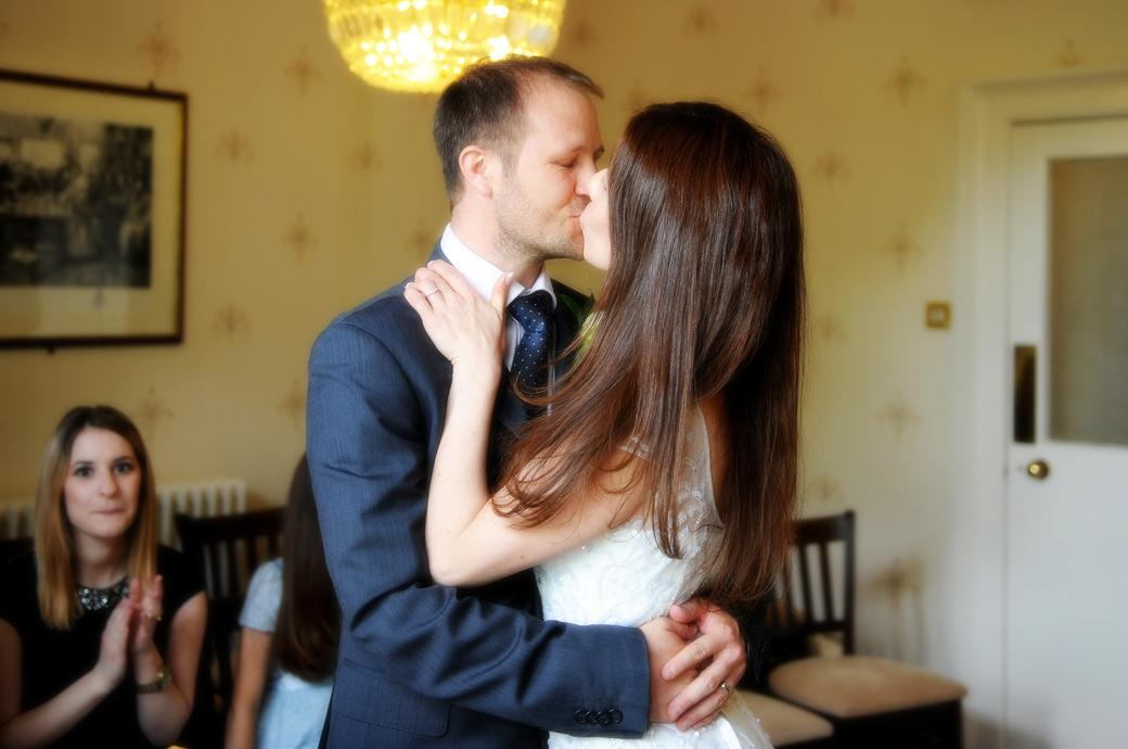 Announced husband and wife the newlywed couple passionately kiss at Guildford Register Office in Artington House by a Surrey Lane wedding photographer
