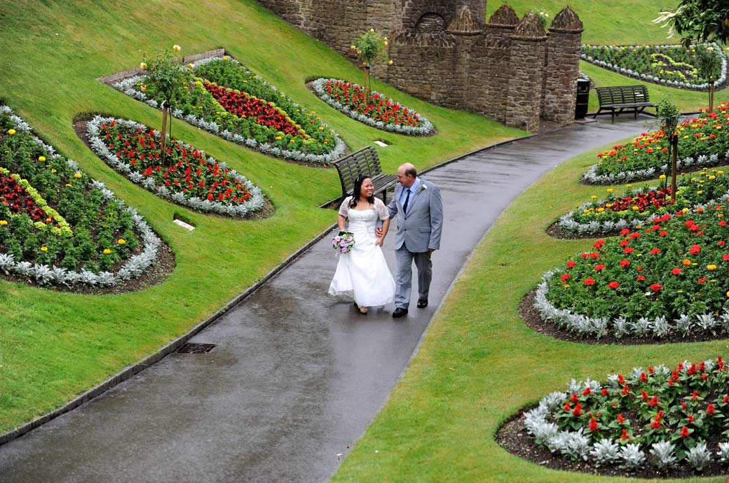Happy newlyweds walking down a wet path through  Guildford Castle Gardens past the colourful flowerbeds after their marriage in Surrey wedding venue Artington House