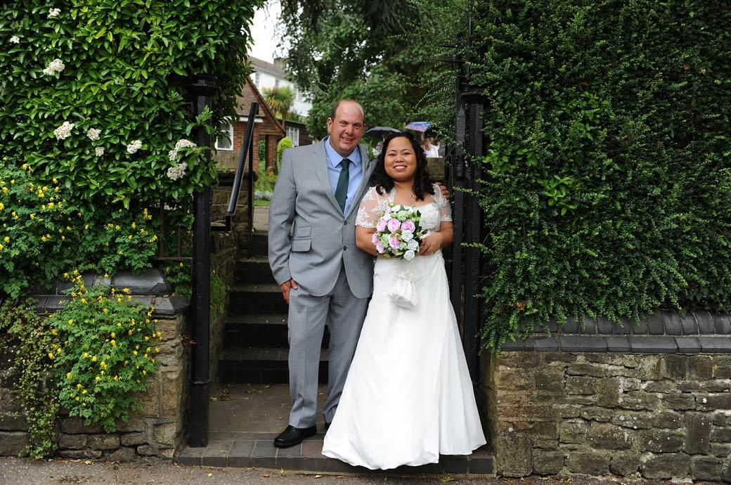 Relaxed and happy bride and Groom take a moment for a wedding picture in the path out of Guildford Castle Gardens in Surrey after their Guildford register office marriage earlier