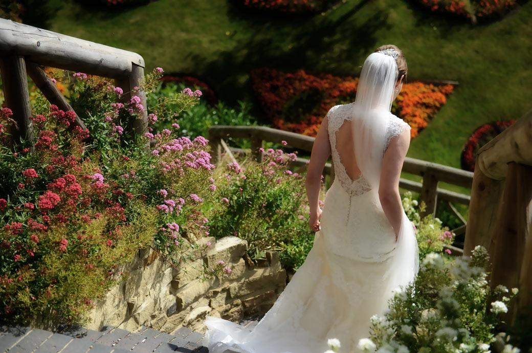 Lovely back shot wedding photo of the Bride and her beautiful dress as she descends the stone steps from Guildford Castle in Surrey to the pretty gardens below