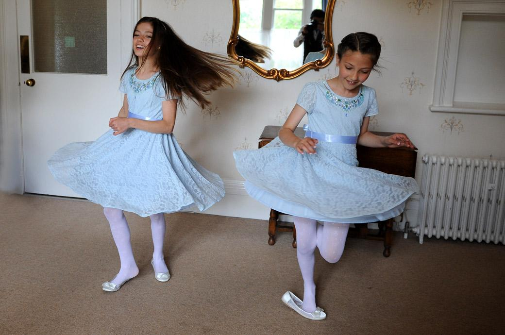 Little bridesmaids swirling around in their pretty blue dresses as they await their mum and dad  in Artington House at Guildford Register Office in Surrey
