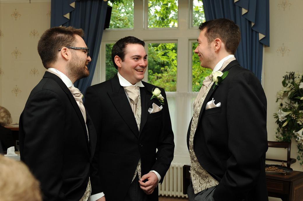 A relaxed Groom having a chat and laugh with his Groomsmen in this wedding photo taken at the Surrey wedding venue  Guildford Register Office in the Guildown Room