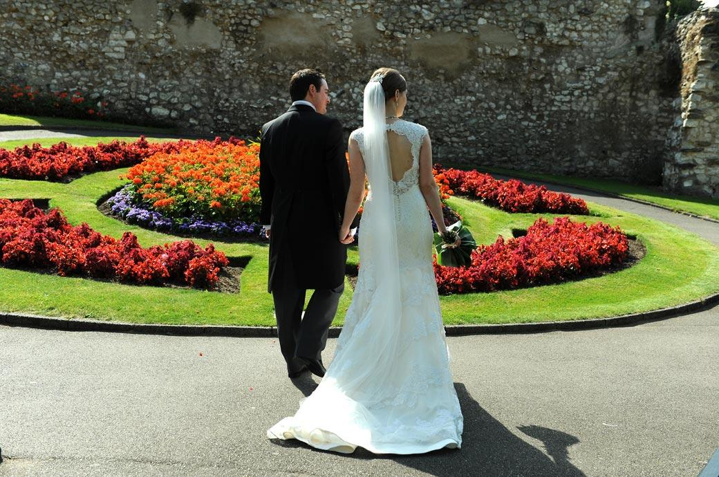 Newly-wed couple standing before a colurful flower bed captured by Surrey Lane wedding photography in this informal wedding photo from Guildford Castle Gardens