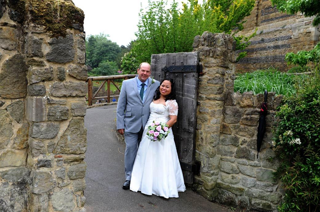 Smiling newlywed couple standing together at the entrance of Guildford Castle Gardens after their earlier marriage at Surrey wedding venue Guildford Register Office