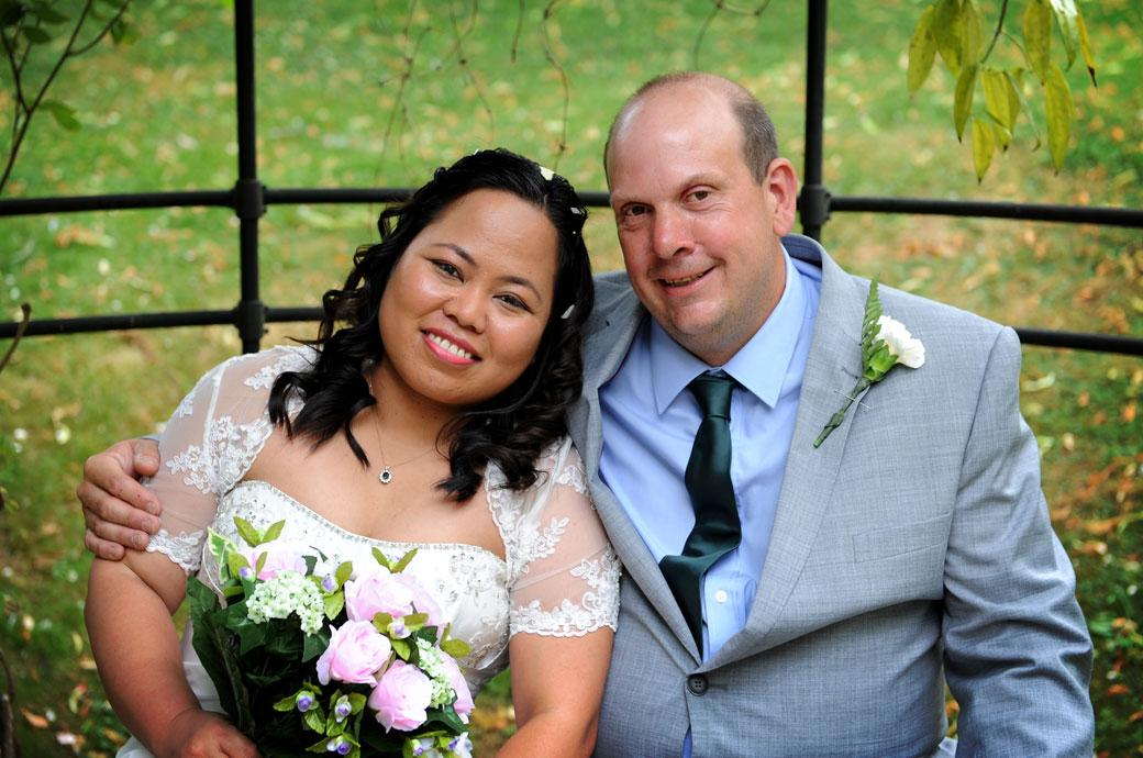 Lovely happy wedding photograph of the smiling couple as they sit together at the front of Surrey Wedding venue Guildford Register Office Artington House in the iron rose arbour