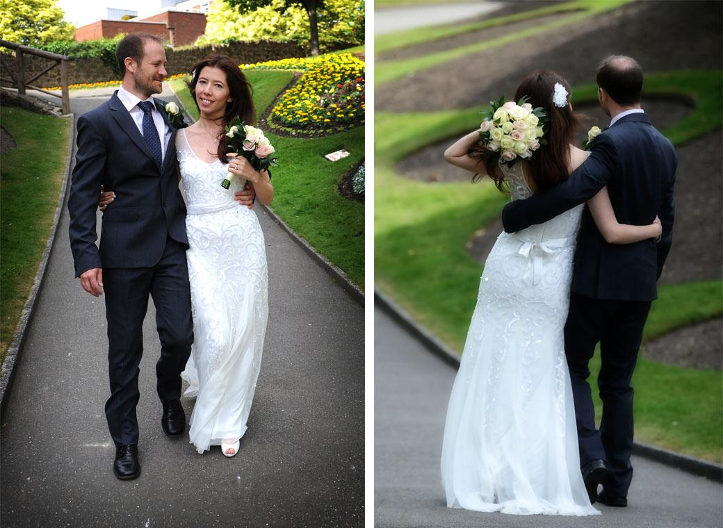 Content and happy Bride and Groom walking arm in arm along the main path in Guildford Castle Gardens Surrey captured in these relaxed wedding photographs
