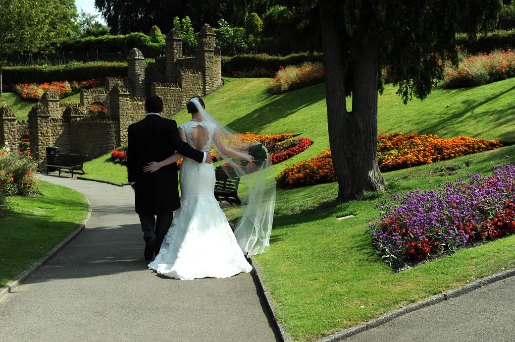 Walking arm in arm with the Bride's veil blowing in the breeze in this lovely wedding picture captured in the colourful and popular Guildford Castle Gardens in Surrey