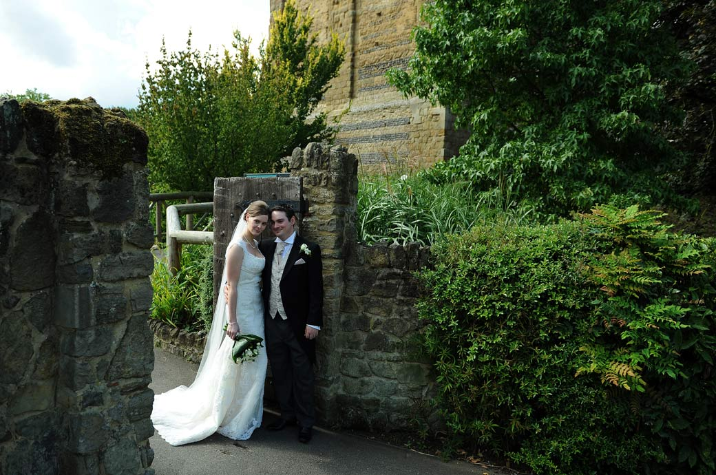Wedding picture by Surrey Lane wedding photographers of the young newly-weds posing by the gate to the ancient and popular Guildford Castle Gardens