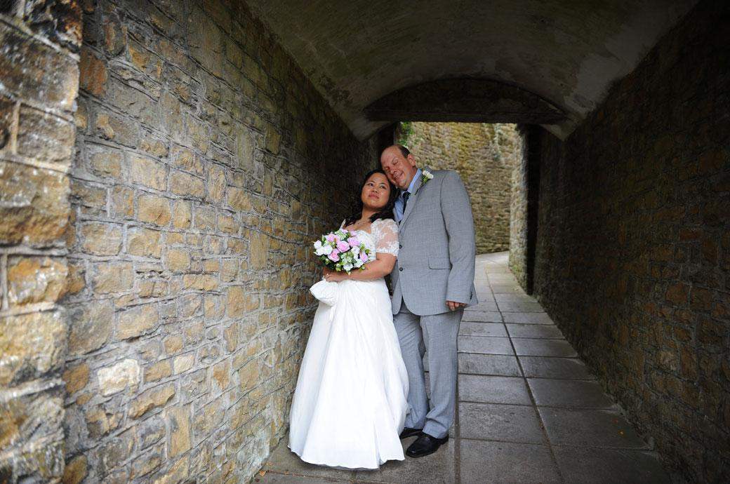 Sheer happiness in this Bride and Groom wedding picture from Guildford Castle Surrey as they shelter from the rain in  the covered alleyway  after their marriage at the register office
