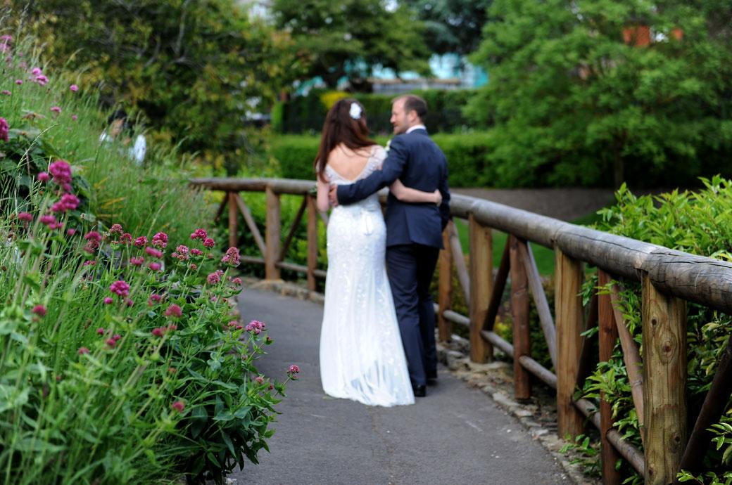Wedding couple walking along a path surrounded by greenery and flowers in the beautiful and tranquil Surrey gardens of the historic Guildford Castle