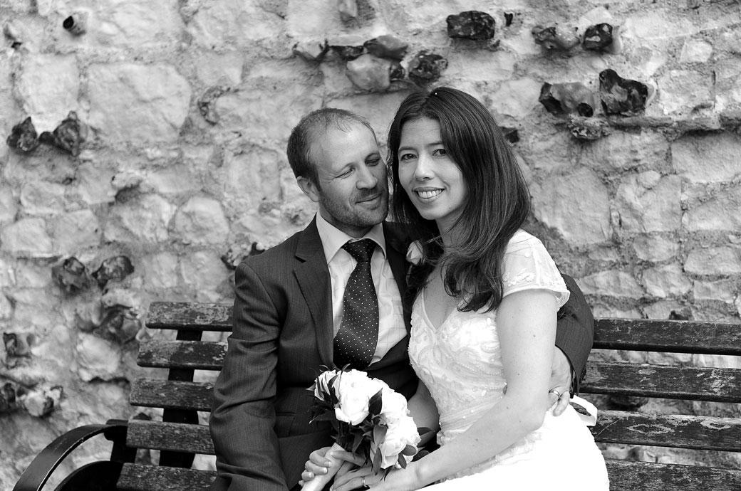 The happy smiling bride sits by her proud husband on a park bench in Guildford Castle Gardens in Surrey after their marriage at Guildford Register Office
