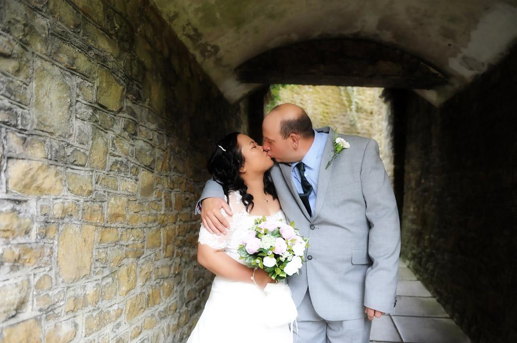 Romantic kiss for the Bride and groom as they take shelter from the rain in the covered alleyway in Guildford Castle Gardens in Surrey after their Guildford register office wedding