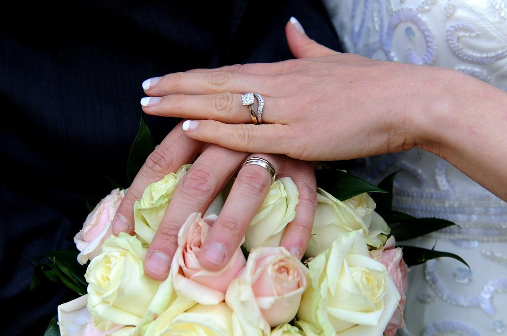 Wedding rings on display on a bouquet background of pink and yellow roses taken by a Surrey Lane wedding photographer at Guildford Register Office Artington House