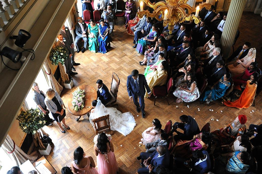 Looking down on the marriage ceremony in the Main Hall  at Hampton Court House next to Bushy Park in Surrey from the first floor balcony