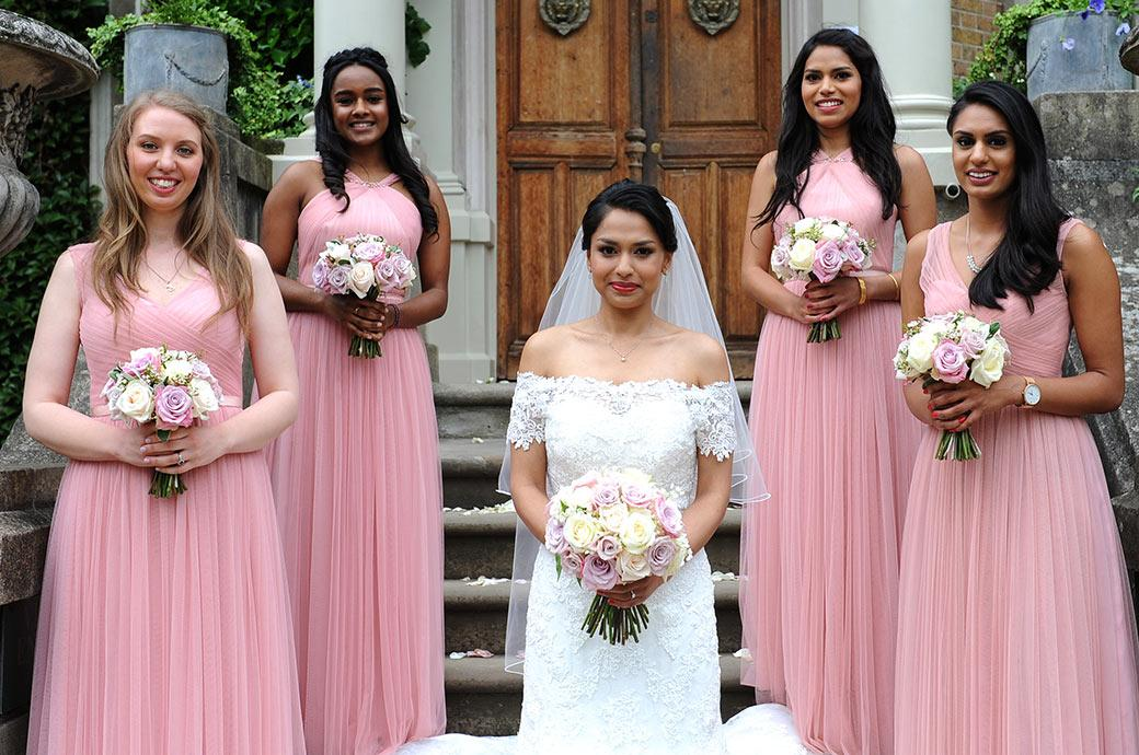 Bride stands on the steps of the grand looking Surrey wedding venue Hampton Court House with her Bridesmaids in pink flanking her