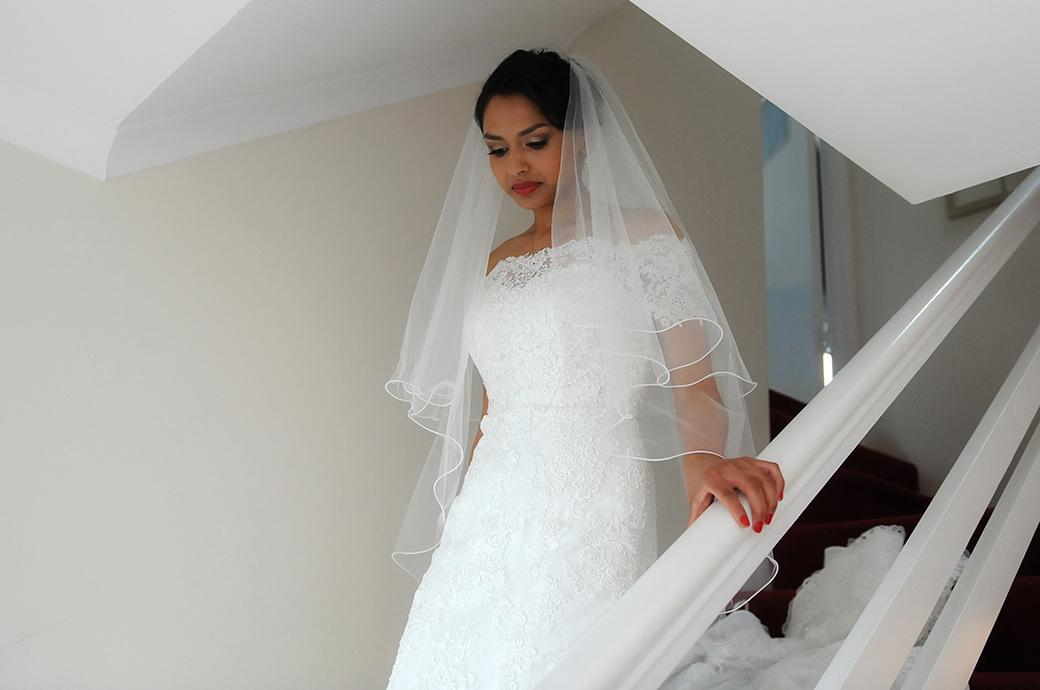 Beautiful elegant Bride descends from her bedroom at her parents ready to leave for her marriage at Hampton Court House a Surrey wedding venue of great renown