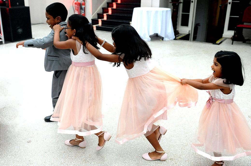 Children having fun as they play together on the dancefloor in the Ballroom at Surrey wedding venue Hampton Court House during the drinks reception
