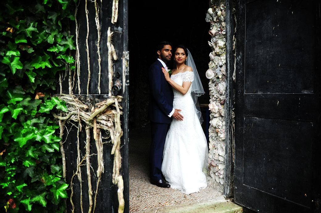 Romantic view in this wedding picture from Surrey venue Hampton Court House beyond the vine covered door of the Bride and Groom embracing in the doorway of the shell grotto