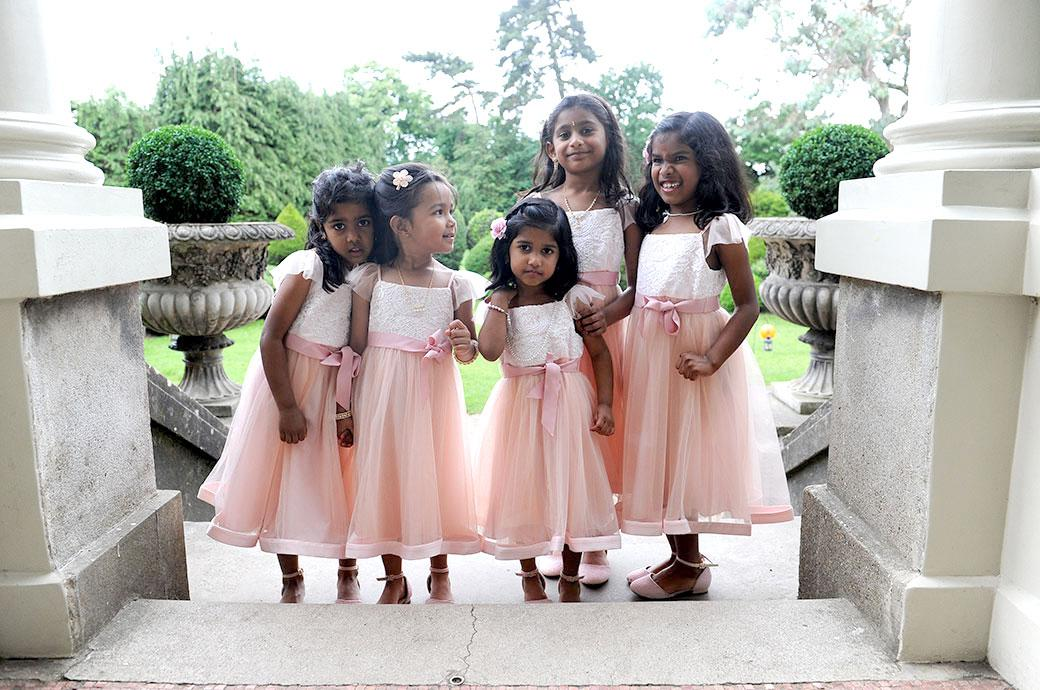 Cute little flower girls captured in this wedding photo taken at Hampton Court House Surrey patiently waiting at the top of the steps  for the arrival of the Bride