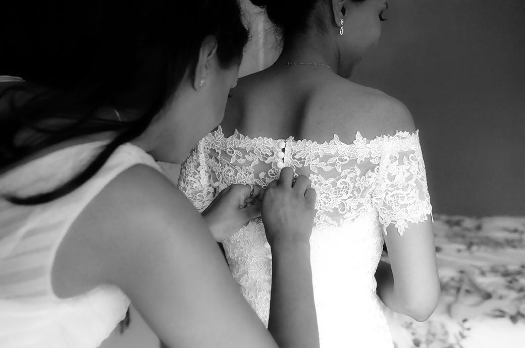 Back shot of a bride having her wedding dress buttoned up by a bridesmaid before leaving for her marriage at Hampton Court House next to Bushy Park in Surrey