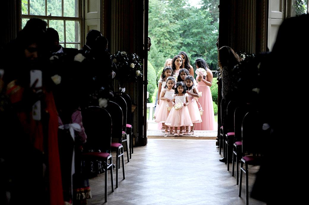Wedding photo of the flower girls and Bridesmaids lined up on the steps of Surrey wedding venue Hampton Court House ready to walk down the aisle of the Main Hall