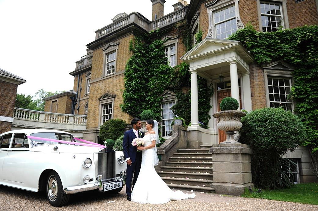 Newlyweds enjoy a moment of fun together as they stand outside the romantic wedding venue Hampton Court House in Surrey next to their white Rolls Royce
