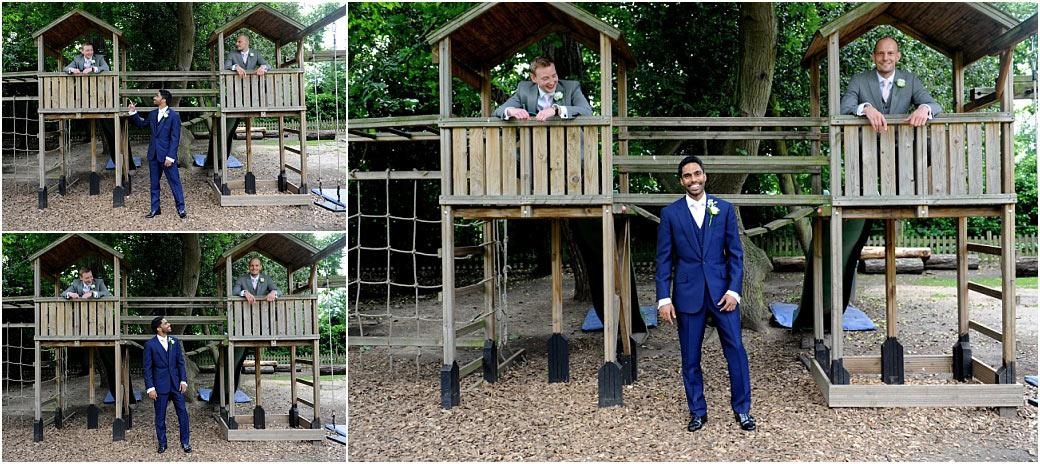 Groom and Groomsmen have some fun in the grounds Surrey wedding venue Hampton Court House as they play around the children's' climbing frame