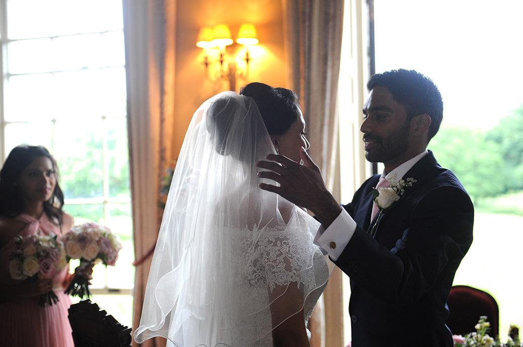 Groom looks into the eyes of his Bride after removing her wedding veil captured at the romantic Hampton Court House wedding venue next to Bushy Park in Surrey