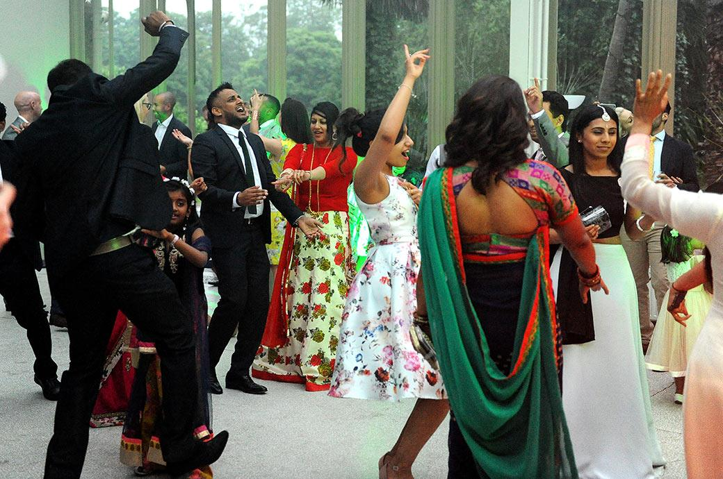 Guests in colourful clothes raise their hands in the air as they dance with passion in the Conservatory at Hampton Court House over the road from Hampton Court Palace in Surrey