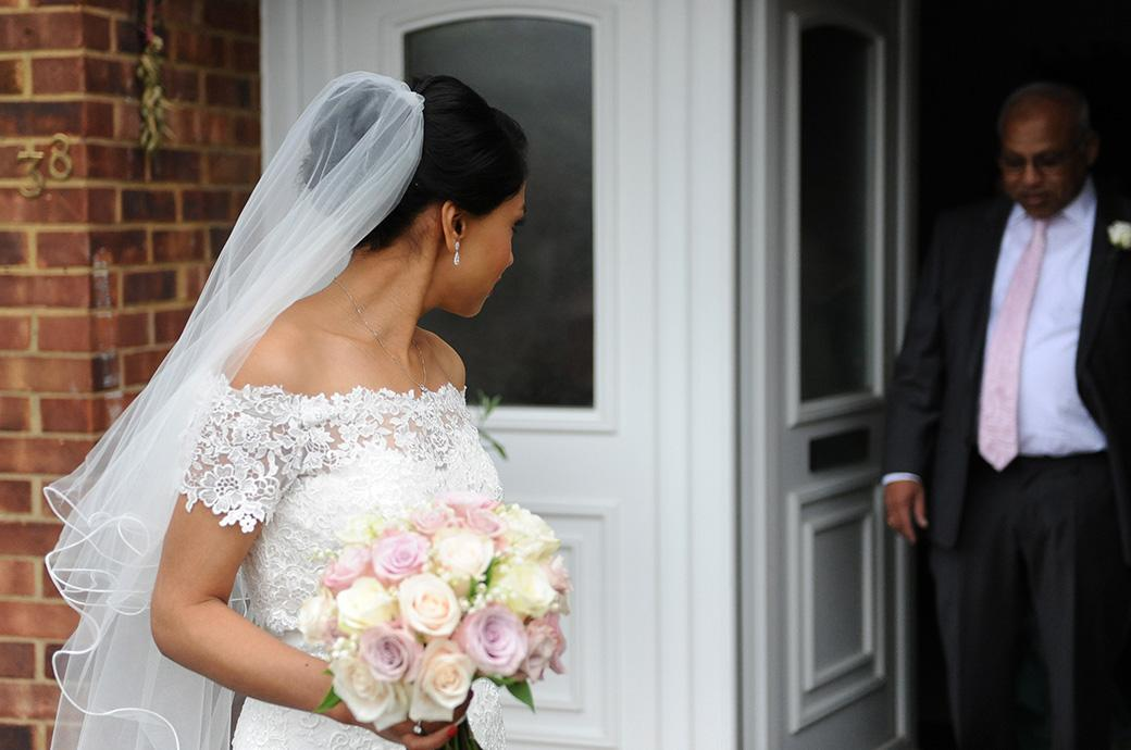 Bride captured in this wedding photograph as she waits for her father to leave the house on their way for her marriage at Hampton Court House in Surrey