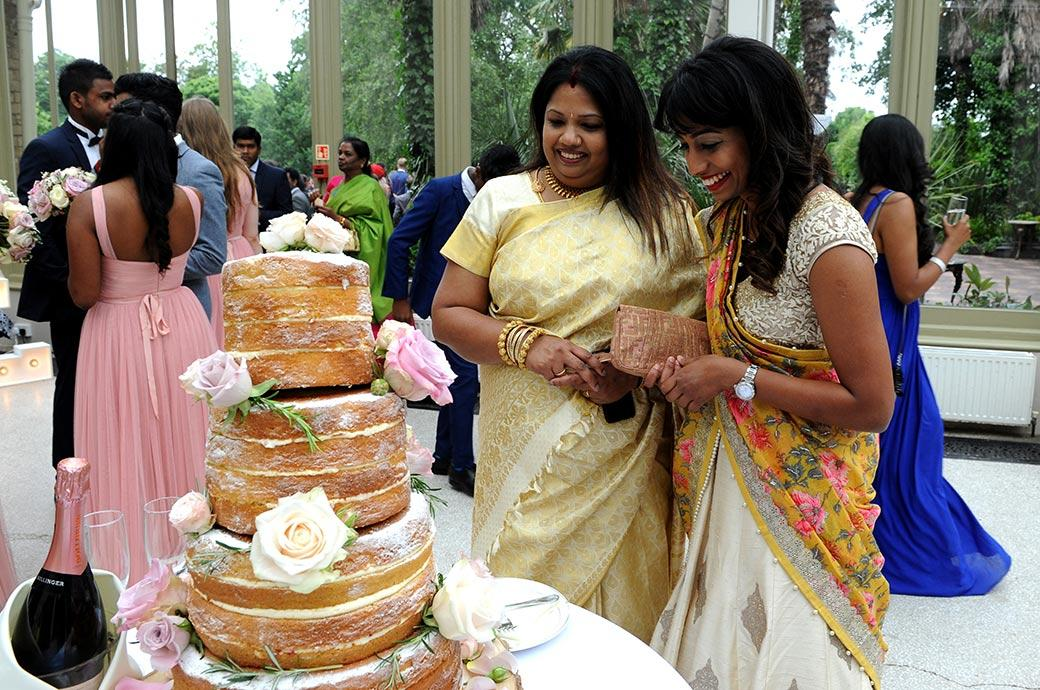 Wedding photograph of ladies in bright saris at Surrey venue Hampton Court House admiring the wedding cake on show in the Conservatory