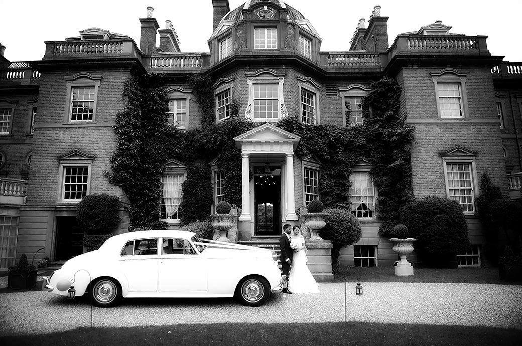 Distant wedding photo of a bride and groom at Surrey wedding venue Hampton Court House standing by their classic Rolls Royce wedding car on the drive