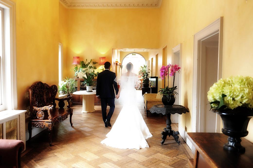 A romantic wedding photograph captured at Surrey wedding venue Hampton Court House of the Bride and groom hand in hand as they walk down the corridor for the reception