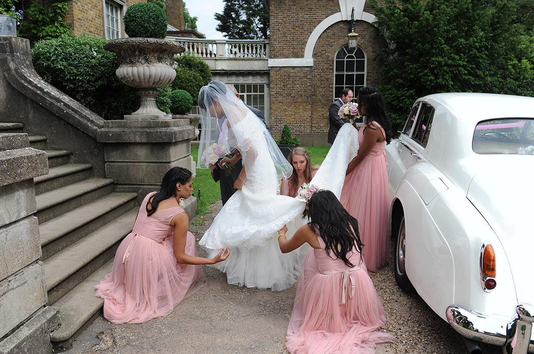 Bridesmaids spring into action straightening out the Bride beautiful wedding dress on the drive at Hampton Court House Surrey a wedding venue next to Bushy Park
