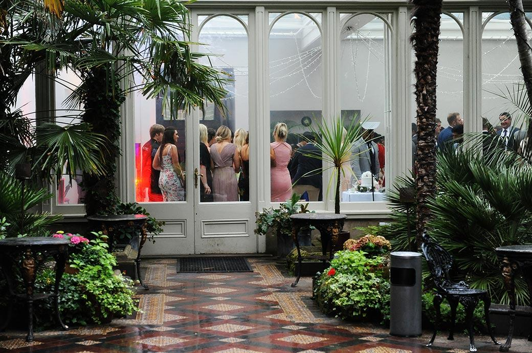A picture of guests at Surrey wedding venue Hampton Court House captured on the dance floor in the Conservatory taken through the windows from the Winter Garden