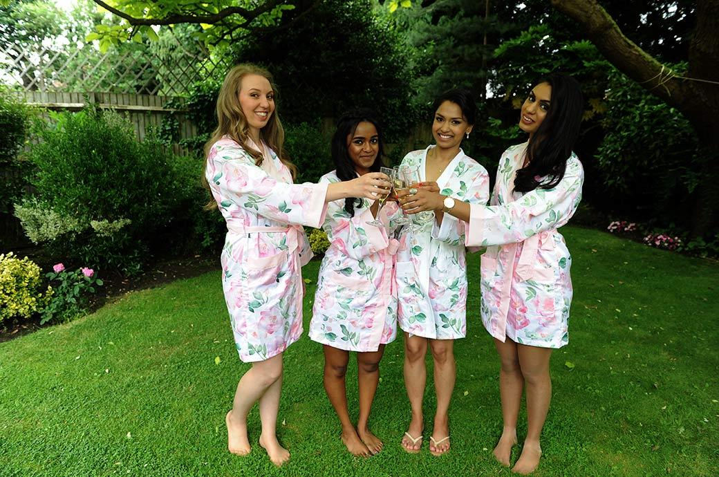 Bridesmaids dressed in their floral dressing gowns toast the Bride with champagne before getting ready and leaving for the wedding venue at Hampton Court House in Surrey