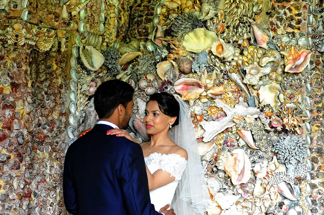 Smiling Bride holds the Groom's shoulders and looks into his eyes taken at Surrey wedding venue Hampton Court House in the fascinating and colourful Shell Grotto